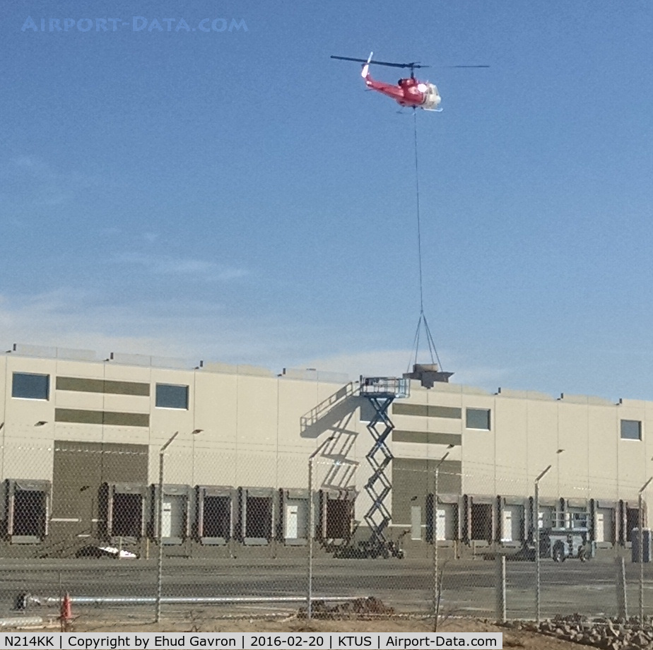 N214KK, 1964 Bell UH-1H C/N 64-13560, N214KK lowering an HVAC unit at distribution facility roof, 1 mile NE of Tucson International Airport.