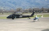 85-24452 @ UKI - CA ARNG UH-60A taxying w/1991 Robinson R22 BETA at Ukiah, CA - by Steve Nation