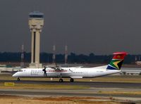 ZS-NMS @ FAJS - South African Airways Dash 8 lands at Johannesburg against the backdrop of threatening skies