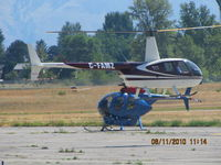 C-FAMZ @ CYKA - ...R-44 hover-taxiing past a long-line equipped MD-500  that is set up for fire-fighting - by Blindawg
