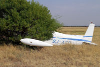 9J-ADO @ FBSK - This has been dumped at Gaborone, Botswana long enough for a tree to grow around it! - by Duncan Kirk