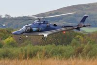 G-WOFM @ EGFH - Visiting helicopter lifting off from Swansea Airport. - by Roger Winser