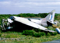 XV786 @ EGDO - Scanned from a print. The remnants of Harrier GR.3 XV786 lie in the Fire Training School at Predannack, Cornwall in 1997. Coded 'S' this a/c had been in use at the SFDO at nearby RNAS Culdrose - by Clive Pattle