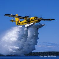 C-FOPJ - Carl Hanssen dropping a load of water - by Bush planes north