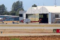 N107Z @ KRDD - 1983 Bell 209 (AH-IS Cobra) Firewatch Cobra C/N 22342 at Redding being pushed back into the hangar. - by Tom Vance