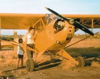 UNKNOWN @ SQL - I am giving this J3C-65 a thorough inspection with my sister looking on. This was at San Carlos airport around 1960-61 when most planes were parked on dirt like this Cub is. - by S B J