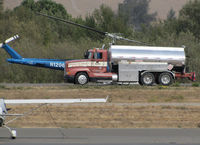N1206G @ O69 - DON'T THINK THIS THING WILL FLY! Trans Aero (Cheyenne, WY) 1966 Bell UH-1H taking a break behind the fuel truck at Petaluma Municipal Airport, CA temporary home base while making water drops on the devastating October 2017 Northern California wildfires - by Steve Nation