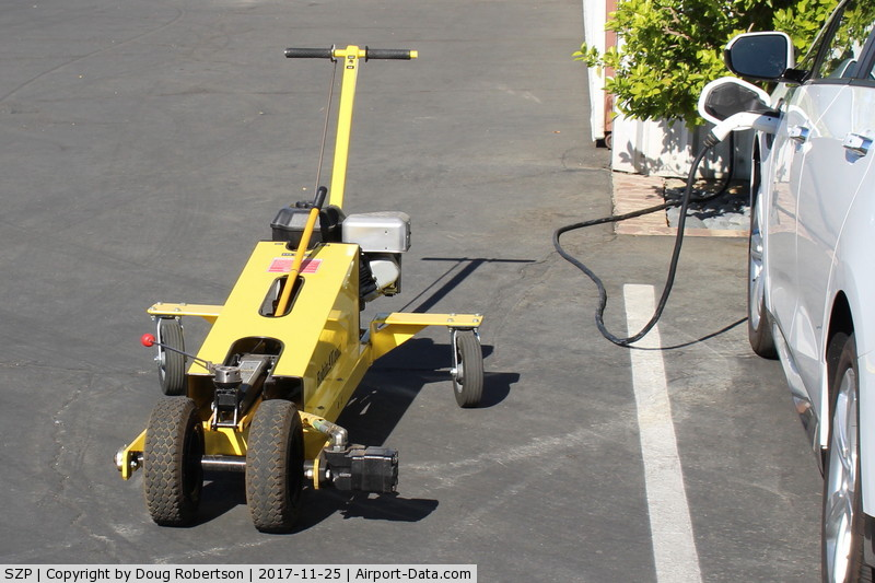 Santa Paula Airport (SZP) - This powered dolly moves a Robinson R44 helicopter in and out of its SZP hangar. Dual handle is for steering.