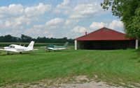 Trinca Airport (13N) - Two small planes sit on the apron by the hangar; the grass strip is in the background. - by Daniel L. Berek