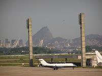 Galeão - Biz jet on ramp at Rio. Sugar Loaf Mountian in background. - by John J. Boling