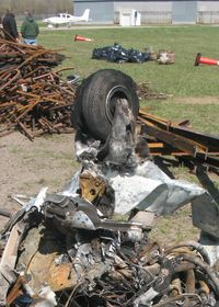Crystal Airport (MIC) - The remains of a Piper PA-28 after a hangar fire.  Note the fiberglass cloth from the nose wheelpant survived, but the resin has melted away. - by Timothy Aanerud
