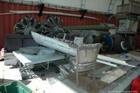 Shell Creek Airpark Airport (F13) - Various Douglas DC-3 parts in the open hangar. - by Carl Byrne (Mervbhx)