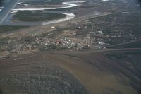 Fort Yukon Airport (FYU) - Fort Yukon, Alaska.  Minor flooding of ramp during breakup of Yukon River.  (River seen in picture flows into the Yukon which is to the left of the image)  Taken from Wright Air N4637U piloted by Dave Lorring. - by David Lee