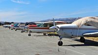 South County Arpt Of Santa Clara County Airport (E16) - Long line of locally-based single engine pistons at South County Airport, San Martin, CA. Most of these aircraft are non airworthiness. - by Chris Leipelt