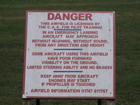 Compton Abbas Airfield - sign next to public footpath style across runway! - by magnaman